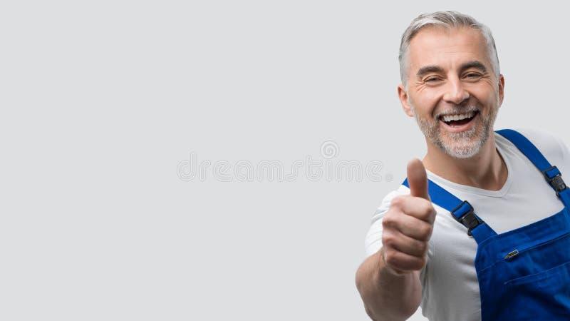 Uśmiechnięty repairman dawać aprobaty obrazy royalty free