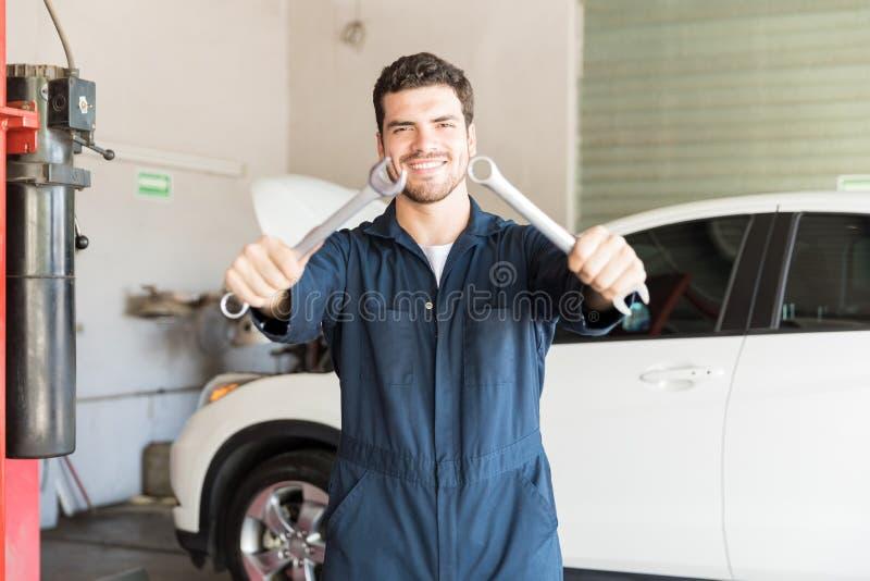 Uśmiechnięty Repairman Pokazuje kombinacj wyrwania Przy Auto garażem zdjęcia stock