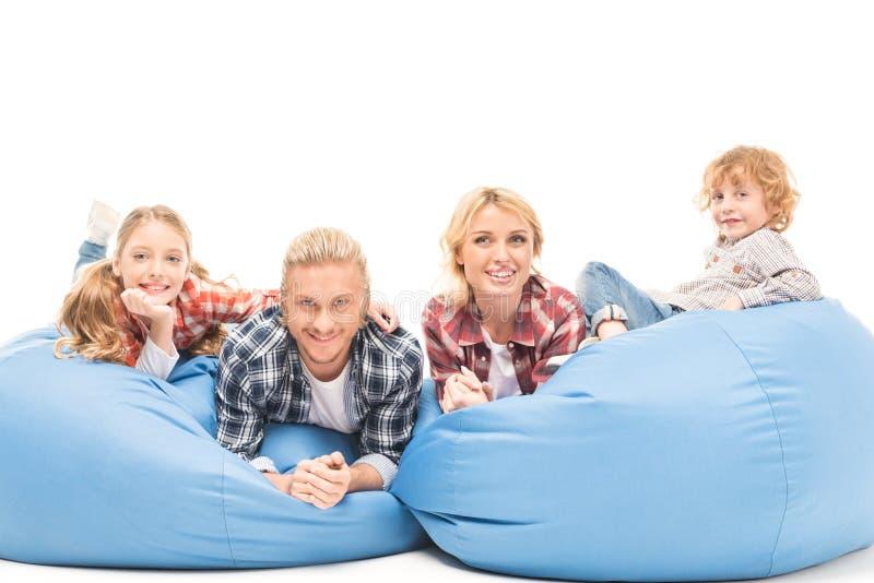 uśmiechnięty rodzinny odpoczywać na bobowej torby krzesłach i patrzeć kamerę obrazy stock