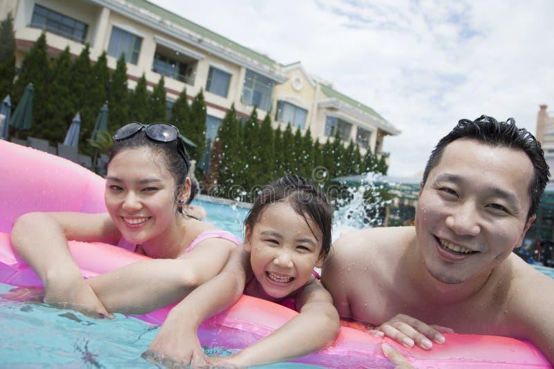Uśmiechnięty rodzinny portret w basenie, ojcu, matce i córce, fotografia stock