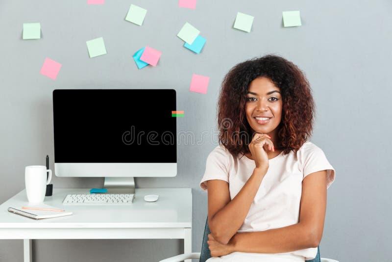 Uśmiechnięty rozważny afrykański kobiety obsiadanie stołem zdjęcia stock