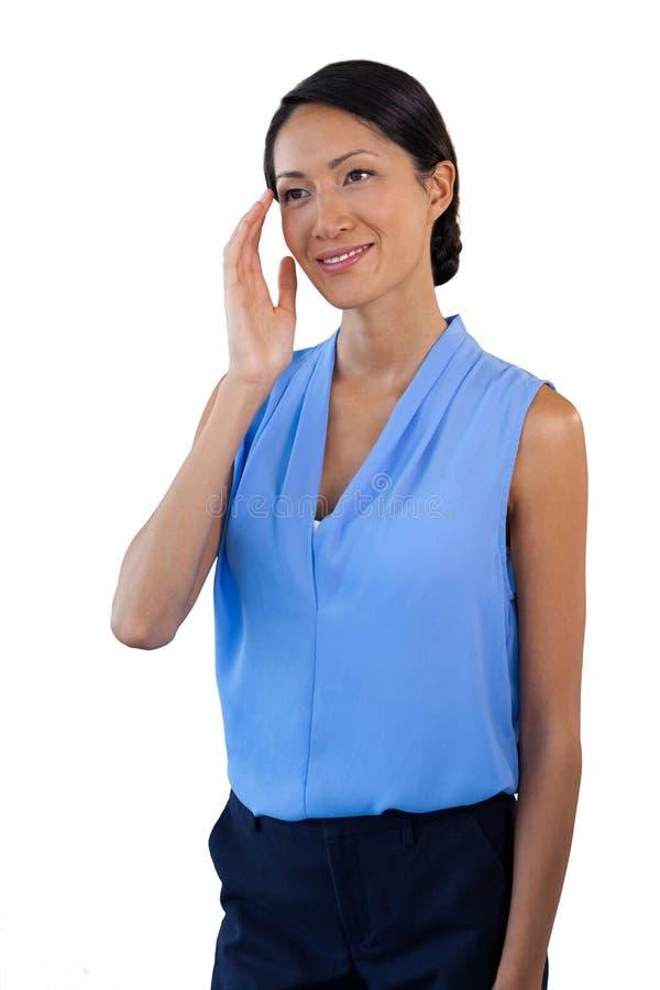 Uśmiechnięty rozważny bizneswoman patrzeje oddalony podczas gdy gestykulujący zdjęcie stock