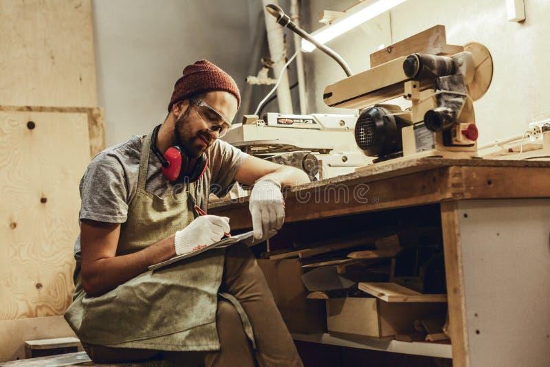 Uśmiechnięty rzemieślnik rysuje blisko workbench fotografia royalty free