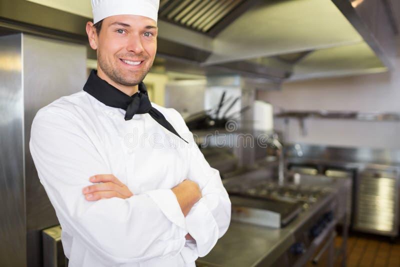 Uśmiechnięty samiec kucharz z rękami krzyżował w kuchni fotografia stock