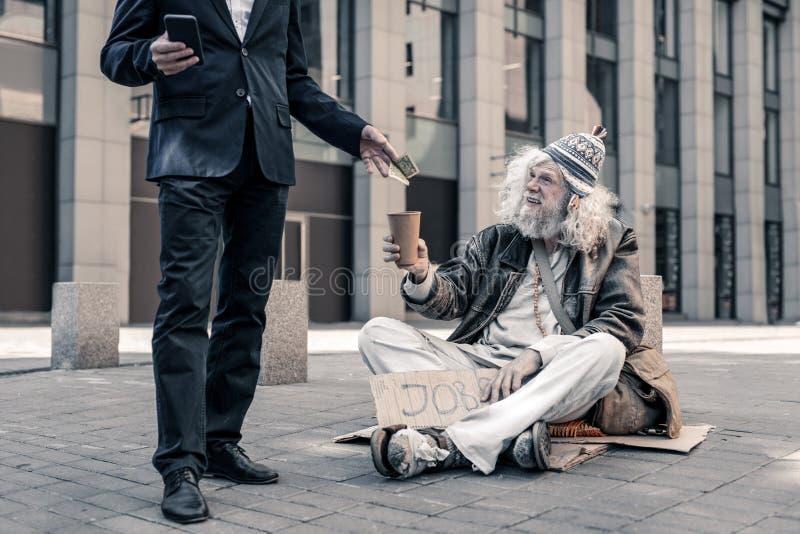 Uśmiechnięty siwowłosy brudny bezrobotny mężczyzny obsiadanie na ziemi obrazy royalty free