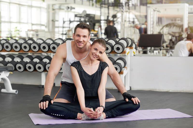 Uśmiechnięty sprawności fizycznej pary obsiadanie na macie przy gym obrazy stock