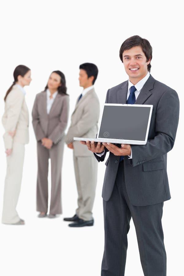 Uśmiechnięty sprzedawca pokazuje laptopu ekran z drużyną za on zdjęcie royalty free