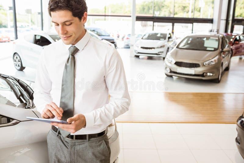 Uśmiechnięty sprzedawca używa pastylkę blisko samochodu zdjęcia stock