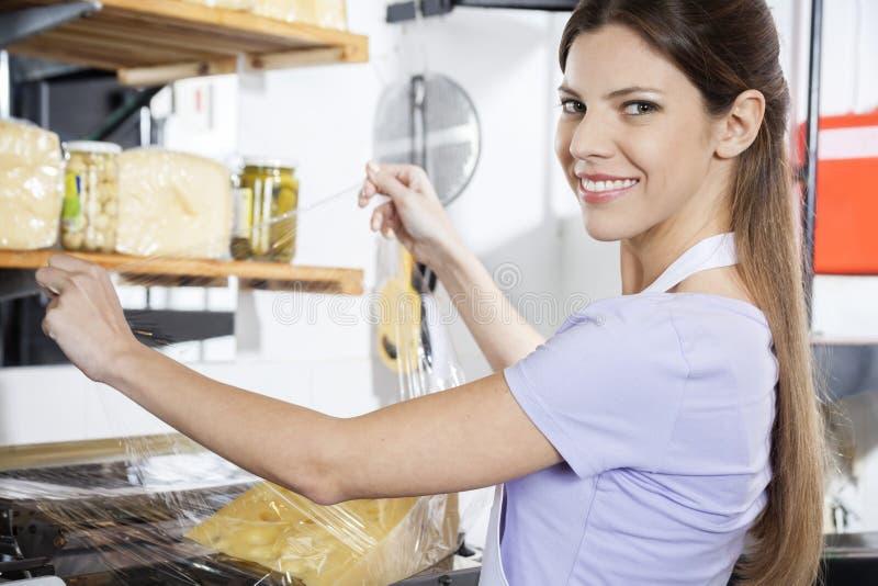 Uśmiechnięty sprzedawczyni kocowania ser Przy sklepem spożywczym obraz stock