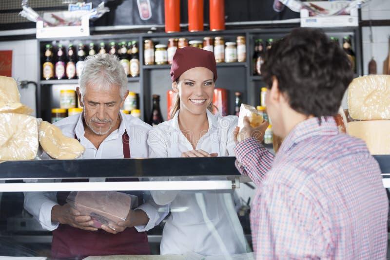 Uśmiechnięty sprzedawczyni porci ser klient W sklepie fotografia royalty free