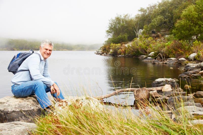 Uśmiechnięty starszego mężczyzna obsiadanie jeziorem fotografia royalty free
