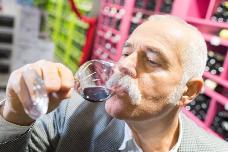 Uśmiechnięty starszego mężczyzny tatsing wino przy supermarketem obrazy royalty free