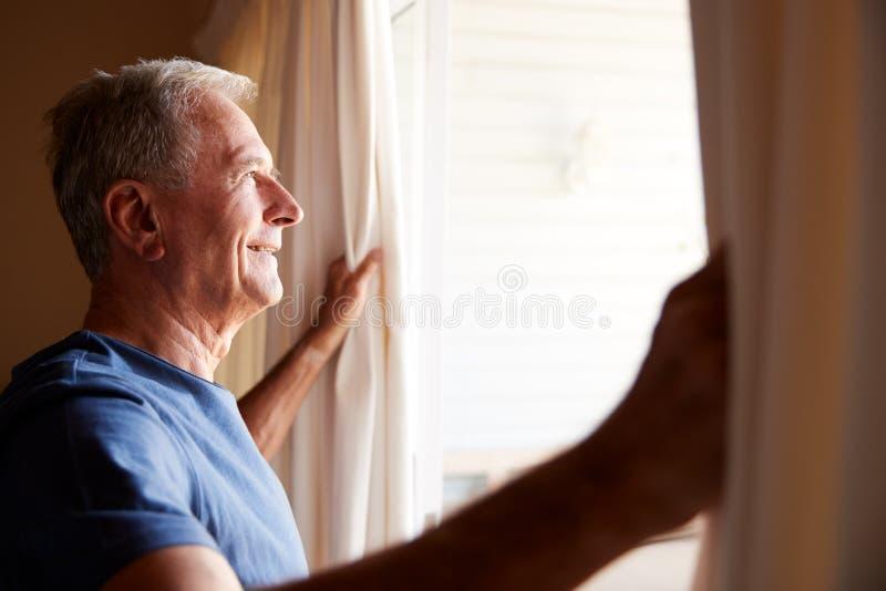 Uśmiechnięty starszy biały człowiek otwiera zasłony na pogodnym ranku, boczny widok, zakończenie w górę zdjęcie stock