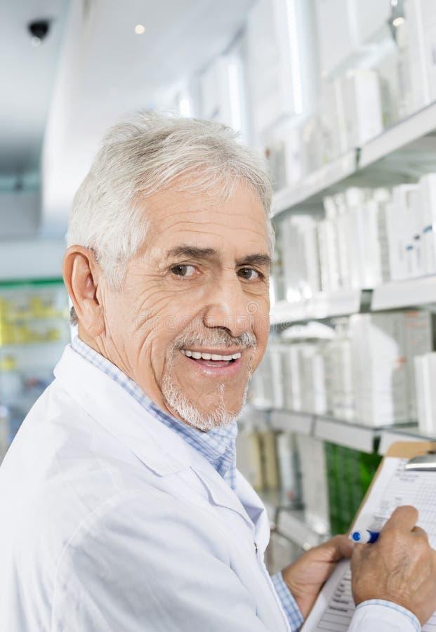 Uśmiechnięty Starszy farmaceuty liczenia zapas W aptece zdjęcia stock
