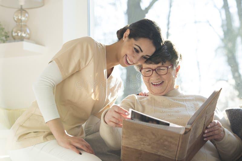 Uśmiechnięty starszy kobiety dopatrywania album fotograficzny zdjęcia stock