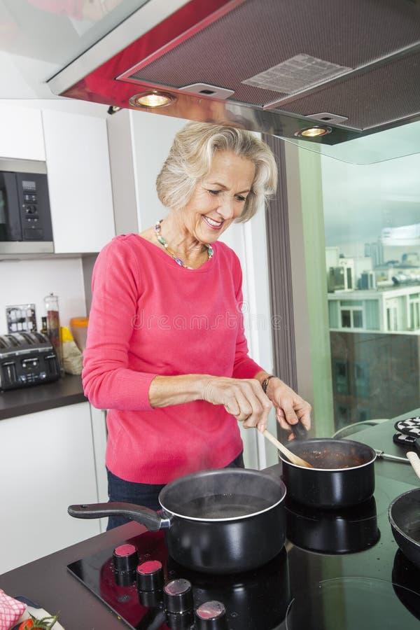 Uśmiechnięty starszy kobiety narządzania jedzenie przy kuchennym kontuarem obrazy royalty free