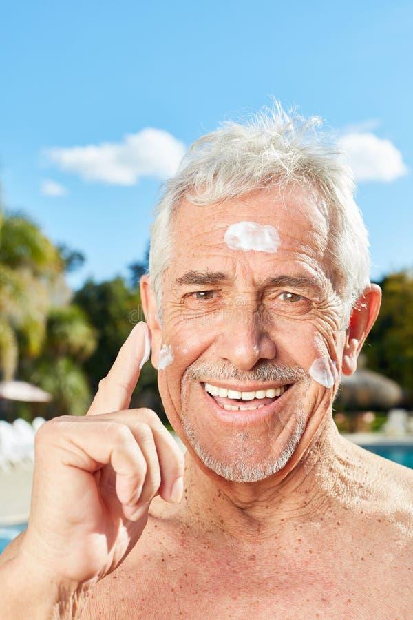 Uśmiechnięty starszy mężczyzna ochrania jego twarz obraz stock