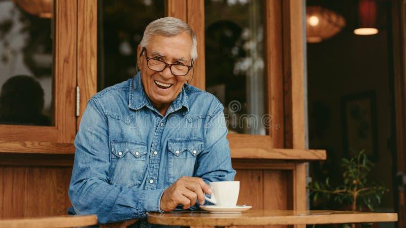 Uśmiechnięty starszy mężczyzna relaksuje przy kawiarnią obraz royalty free