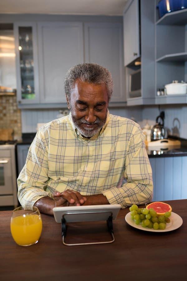 Uśmiechnięty starszy mężczyzna używa pastylka komputer w kuchni fotografia royalty free