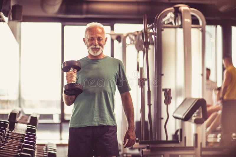 Uśmiechnięty starszy mężczyzna z ciężarem przy gym fotografia stock