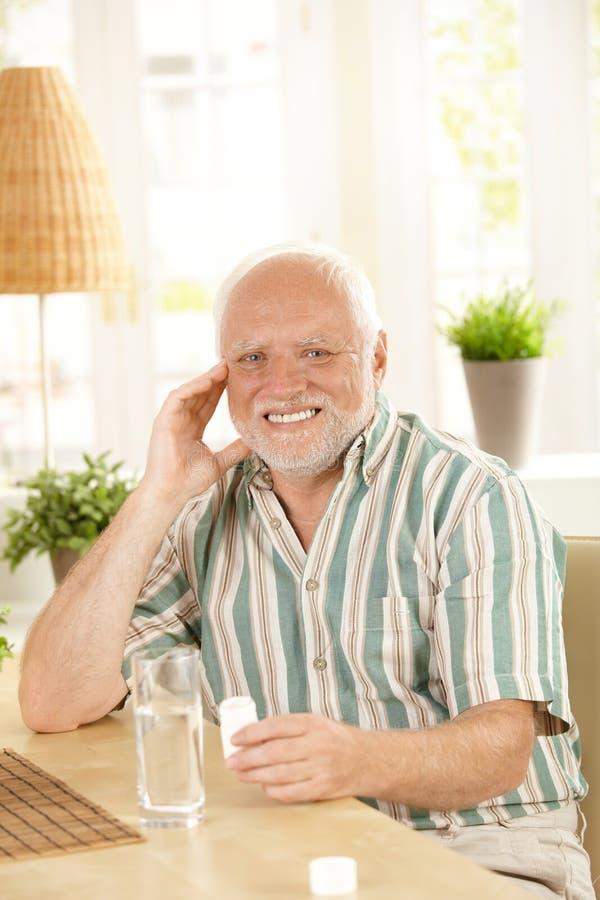 Uśmiechnięty starszy mienia lekarstwo fotografia stock