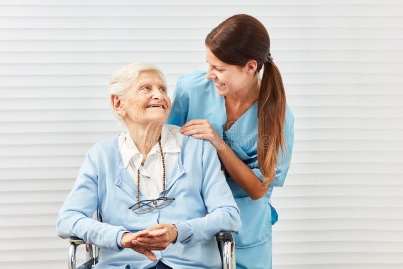 Uśmiechnięty starszy obywatel w wózku inwalidzkim i pielęgniarce zdjęcie royalty free
