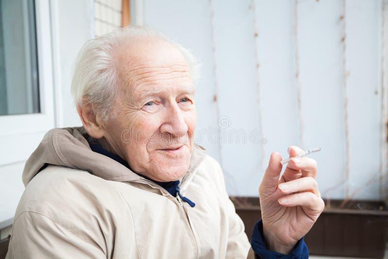 Uśmiechnięty stary człowiek z papierosem fotografia royalty free