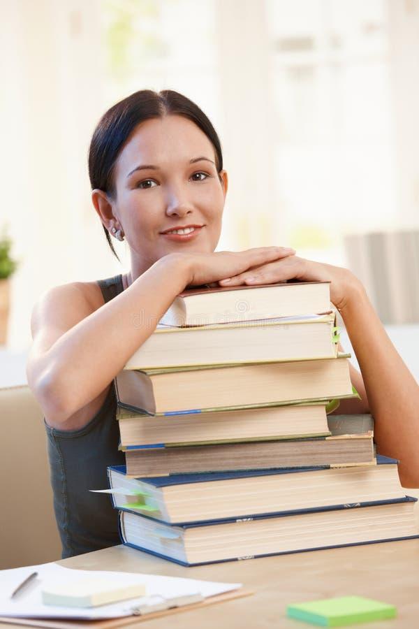 Uśmiechnięty student uniwersytetu z stosem książki zdjęcia stock