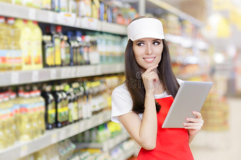Uśmiechnięty supermarketa pracownik Trzyma komputer osobisty pastylkę obrazy stock