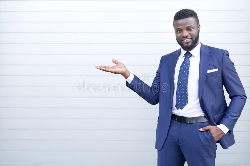Uśmiechnięty szczęśliwy afrykański biznesmen wskazuje coś w kostium pozycji przeciw ścianie obraz stock