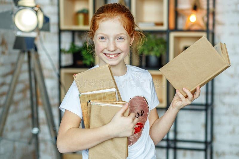 Uśmiechnięty szczęśliwy dziecko trzyma mnóstwo książki Pojęcie lifesty zdjęcia stock