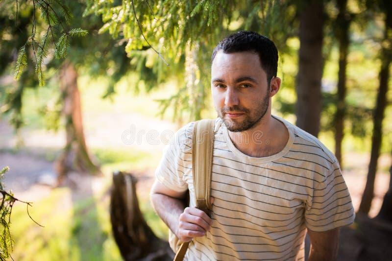 Uśmiechnięty szczęśliwy przystojny mężczyzna z brodą w lesie, góry, park Podróżnika mężczyzna relaksować Podróż stylu życia wycie obraz stock