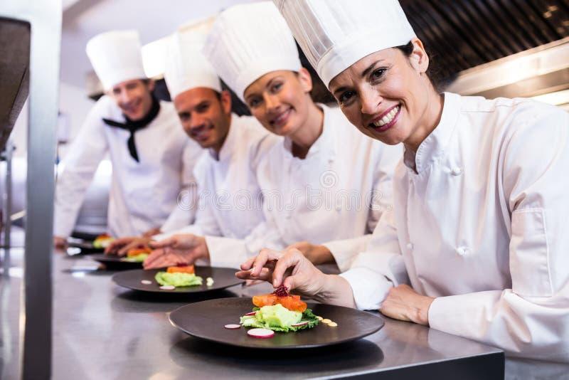 Uśmiechnięty szef kuchni podczas gdy dekorujący jedzenie talerza fotografia stock