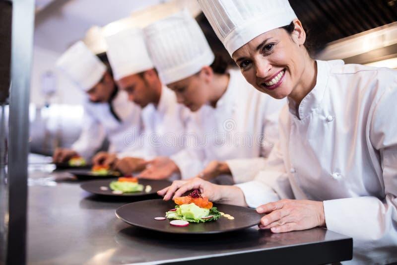 Uśmiechnięty szef kuchni z garnirującym jedzenie talerzem w kuchni zdjęcie stock