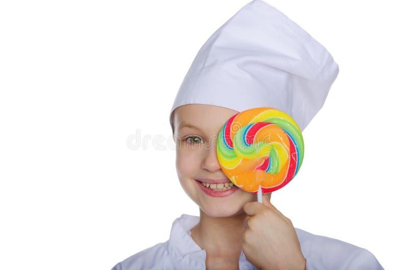 Uśmiechnięty szef kuchni zamykał oko lizaka odizolowywającego na bielu obraz royalty free