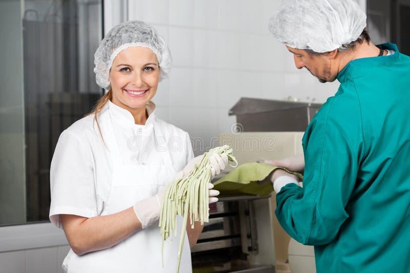 Uśmiechnięty szefa kuchni mienia spaghetti makaron Z obrazy royalty free