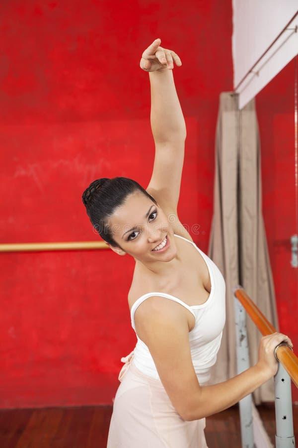 Uśmiechnięty tancerza mienia Barre Podczas gdy Ćwiczyć W Baletniczym studiu zdjęcia stock