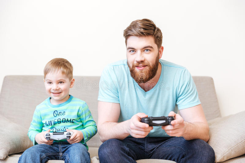 Uśmiechnięty tata i syn bawić się gry komputerowe siedzi na kanapie zdjęcia royalty free