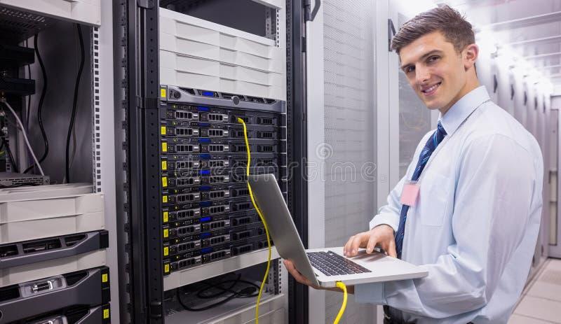 Uśmiechnięty technik używa laptop podczas gdy analizujący serweru fotografia royalty free