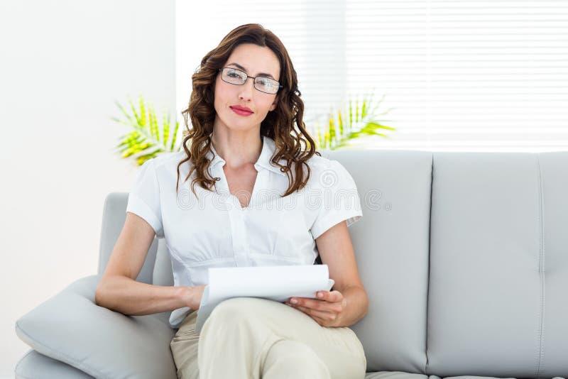 Uśmiechnięty terapeuta bierze notatki zdjęcia stock