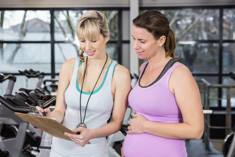 Uśmiechnięty trener pokazuje schowek kobieta w ciąży fotografia stock