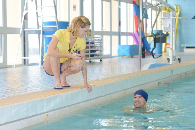 Uśmiechnięty trener pokazuje stopwatch przy pływaczką przy czasu wolnego centrum obraz royalty free