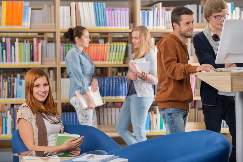 Uśmiechnięty uczeń w bibliotece z przyjaciółmi zdjęcia stock