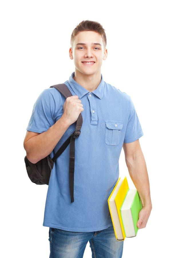 Uśmiechnięty uczeń z książkami i plecakiem odizolowywającymi na bielu zdjęcie royalty free