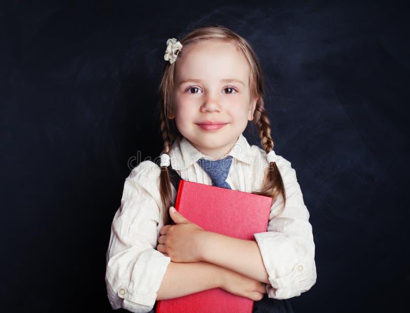Uśmiechnięty uczennica uczeń z książką na błękitnej kredowej desce zdjęcie royalty free
