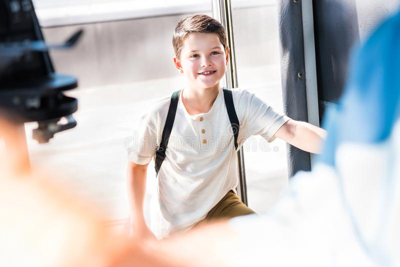 uśmiechnięty uczniowski wchodzić do autobus szkolny i patrzeć zdjęcie stock