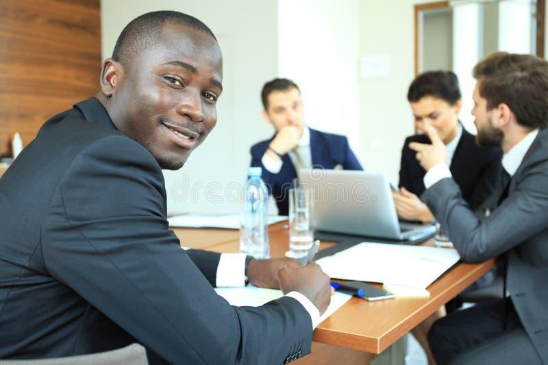 Uśmiechnięty ufny Afrykański biznesmen w spotkaniu z grupą multiracial pracownicy sadzający przy konferencyjnym stołem wewnątrz fotografia royalty free