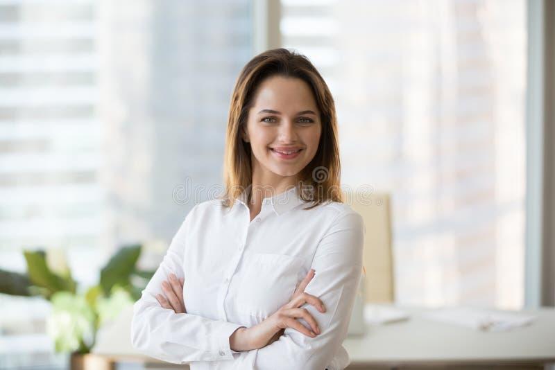 Uśmiechnięty ufny bizneswoman patrzeje kamerę w biurze, hea obrazy stock