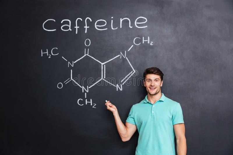 Uśmiechnięty ufny młody uczeń pokazuje chemiczną strukturę kofeiny molekuła fotografia stock