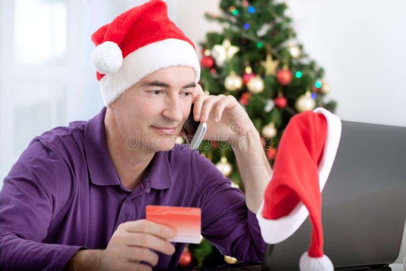 Uśmiechnięty w połowie starzejący się mężczyzna kupuje online teraźniejszość dla bożych narodzeń obrazy stock